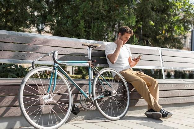 Мужчина отдыхает на скамейке рядом с велосипедом