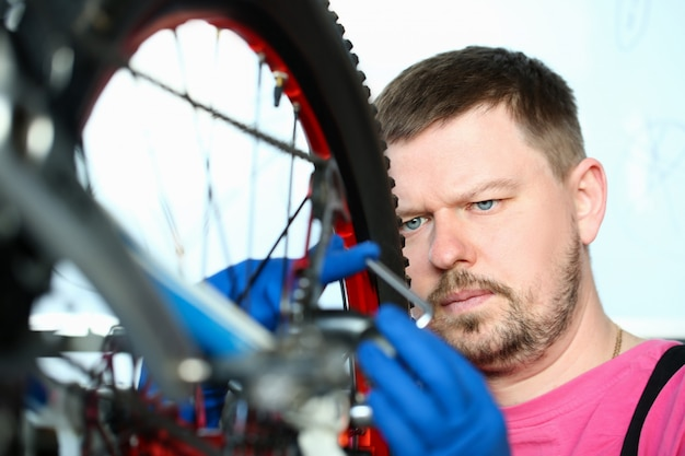 Male repair man bicycle service in blue protective