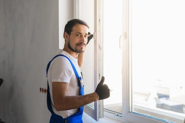 바지를 입은 남성 수리공이 창문을 설치하고 엄지 손가락을 보여줍니다.
