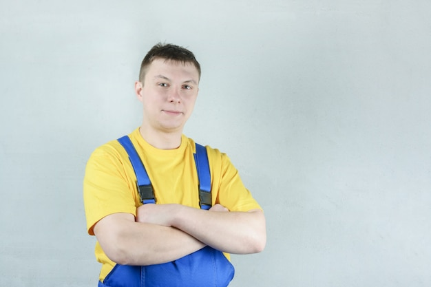 A male repairman in a blue jumpsuit and a yellow t-shirt against a gray wall.