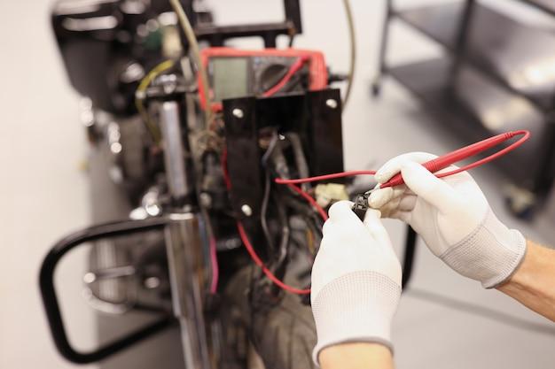 テスタークローズアップ現代のオートバイを使用してオートバイの電気をチェックする男性の修理工