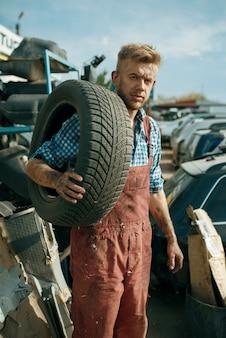 男性の修理工が車の廃品置き場でタイヤを保持しています。自動車のスクラップ、車両のがらくた、自動車のゴミ、放棄された、損傷した、押しつぶされた輸送