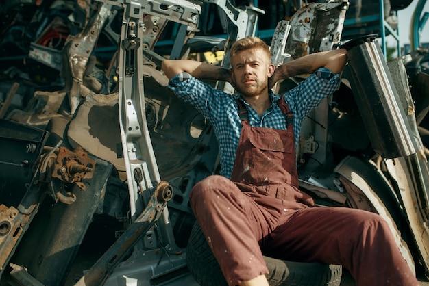 여름 날에 자동차 폐차장에서 편안한 남성 수리공. 자동 스크랩, 차량 쓰레기, 자동차 쓰레기, 버려진, 손상 및 부서진 운송