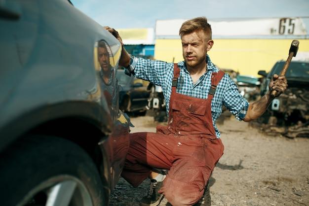남성 수리공은 자동차 폐차장에 망치로 작동합니다. 자동 스크랩, 차량 쓰레기, 자동차 쓰레기, 버려진, 손상 및 부서진 운송