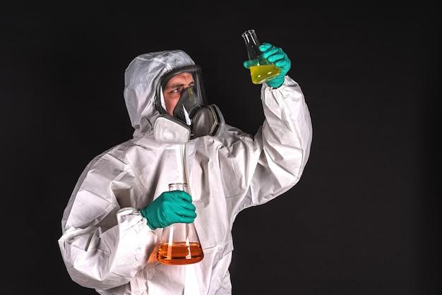 Мужчина-исследователь анализирует жидкий реагент в лабораторной посуде
