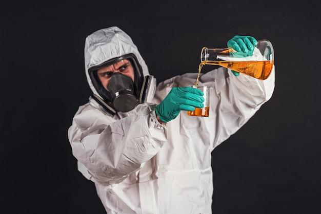 실험실 유리 그릇에 액체 시약을 분석하는 남성 연구원