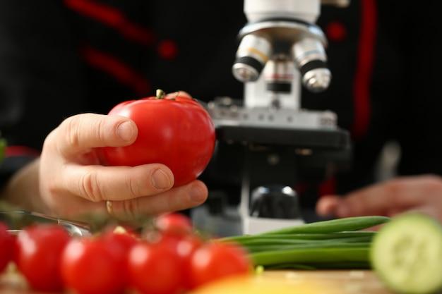 Мужской исследователь держит гмо овощ