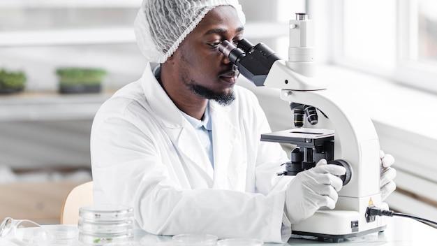 Мужской исследователь в лаборатории биотехнологии с микроскопом