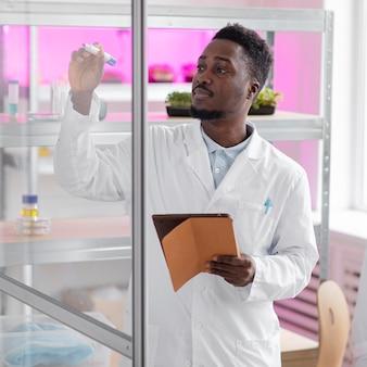 タブレットを使用したバイオテクノロジー研究所の男性研究者