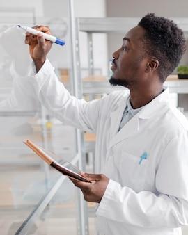 Мужчина-исследователь с планшетом в лаборатории биотехнологии