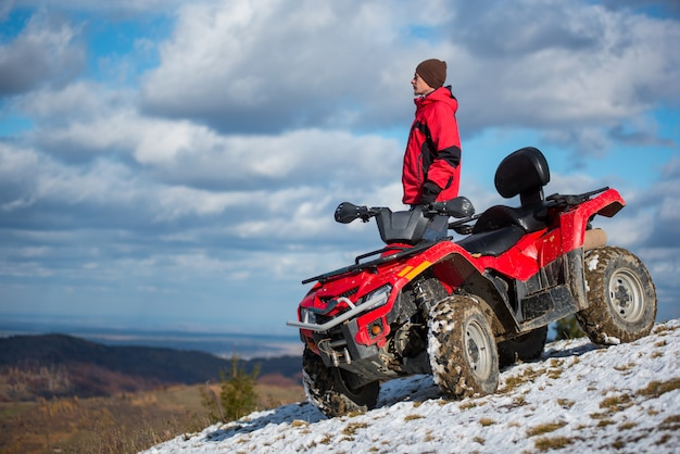 Male rider in a red winter clothes with red quad bike