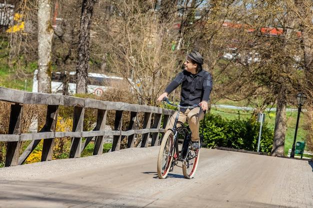 나무 다리에서 자전거를 타고 그의 여행을 즐기는 남성