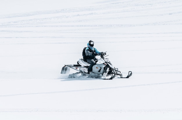 Male riding a snowmobile in a large snowy field