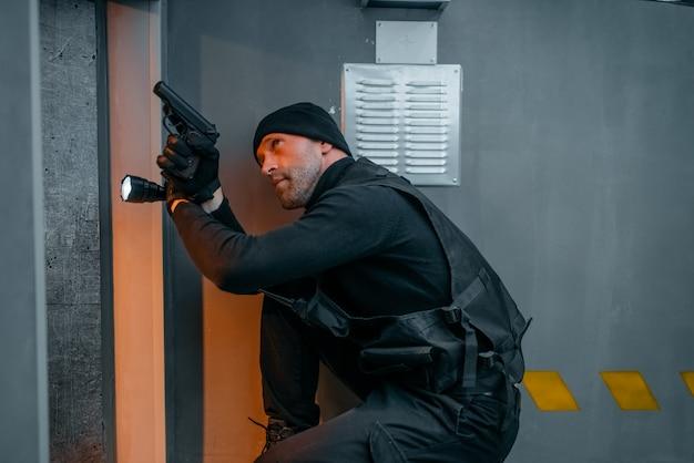 Мужчина-грабитель в черной форме держит пистолет и фонарь