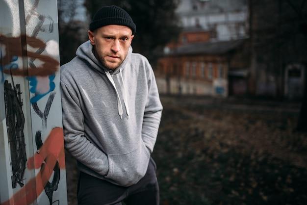 Грабитель-мужчина ждет жертву на ночной улице. понятие преступления, опасность нападения грабежа
