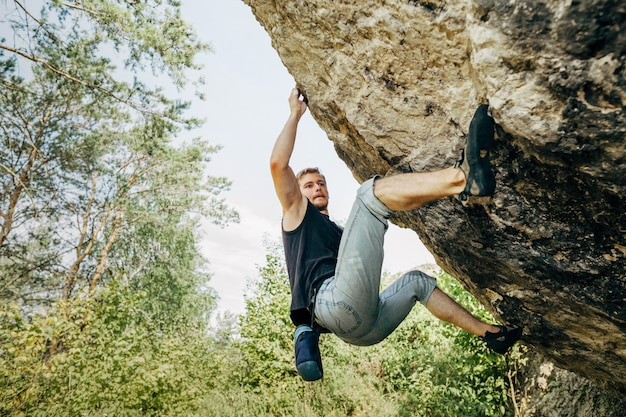 Male rock climber hanging on the cliff