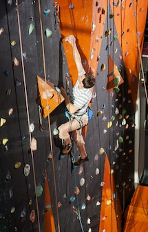 Male rock-climber practicing climbing on rock wall indoors