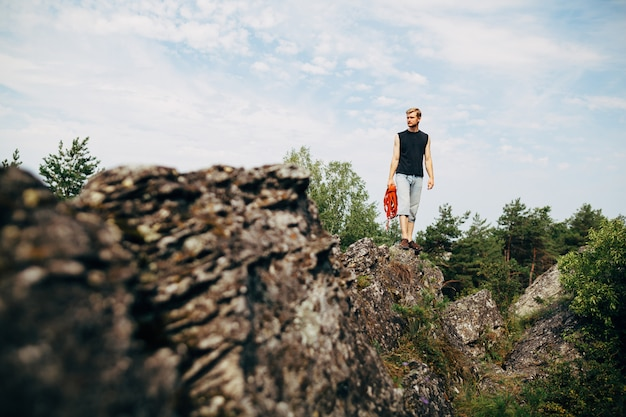 Male rock climber standing on the rock with a rope