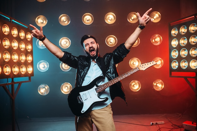 Male rock star with electro guitar hands up on the stage with the decorations of lights.