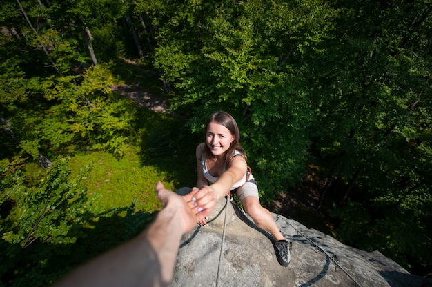 A male rockclimber helping to smiling female climber to reach a peak of mountain