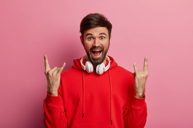 Male rocker enjoys positive vibes, listens rock n roll, cool music in club, uses modern stereo headphones, wears red hoodie, poses against rosy pastel wall, shows horn gesture. body language