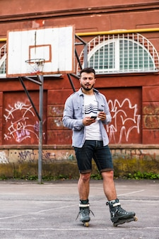 Male rollerskater using mobile phone in basketball court