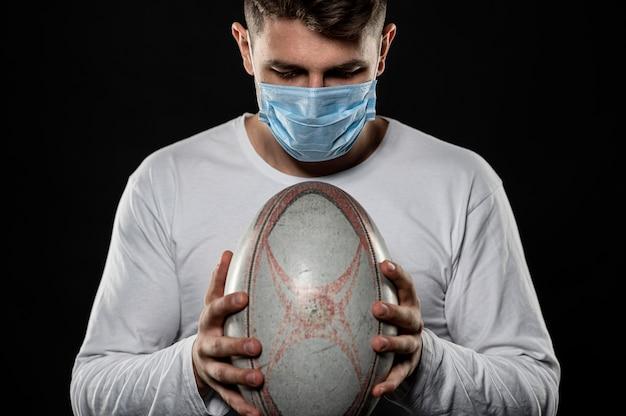 Игрок в регби мужского пола держит мяч в медицинской маске