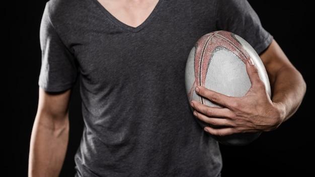 Игрок в регби мужского пола, держащий мяч