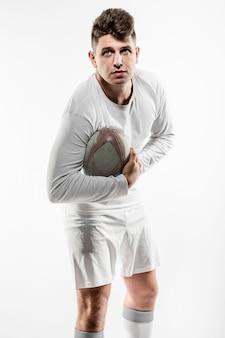 Мужской игрок в регби позирует с мячом