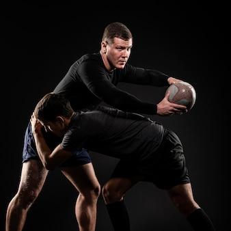 Мужчины-игроки в регби играют с мячом
