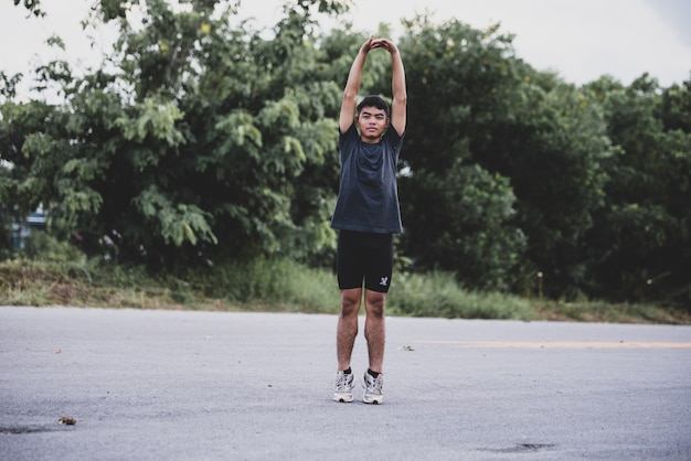 Male runner doing stretching exercise, preparing for workout