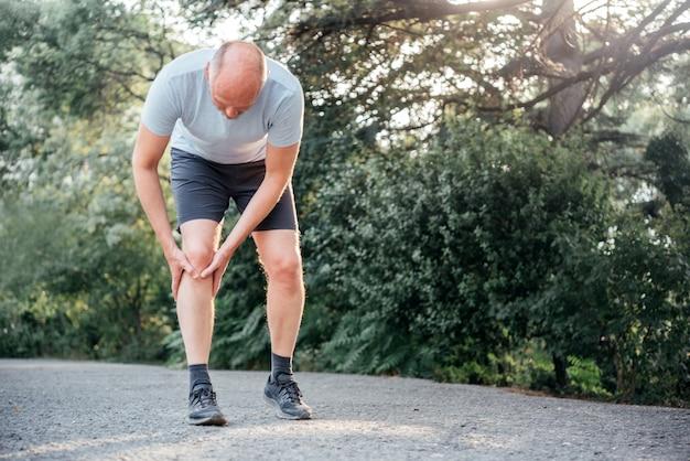 膝を抱えてランナーの膝の怪我に苦しんでいる男性ランナー