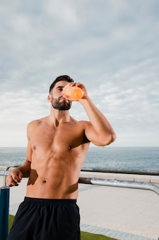 Male runner hydrating while break