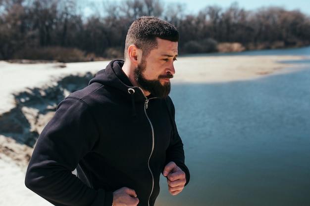男性ランナーは、自然のクローズアップで砂のジョギングの概念を行使しています