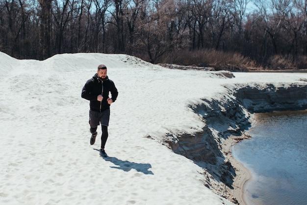 男性ランナーは、砂の自然のジョギングの概念を行使しています