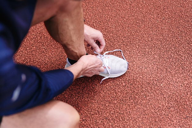 Male runner tying shoe lace after running along the red running track.