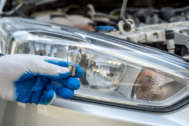 Рука мужчины, держащая лампочку автомобильных фар для ремонта авто, крупным планом.