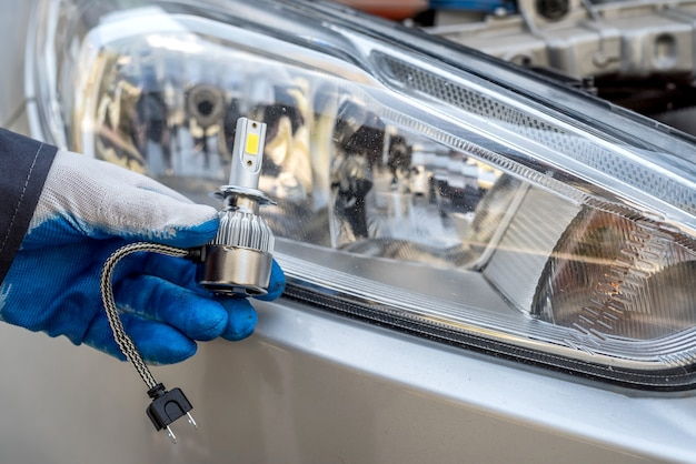 修理自動車用車のヘッドライトの電球を持っている男性の手、クローズアップ