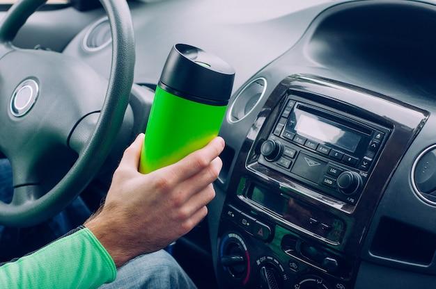 サーモマグカップを持っている男性の手