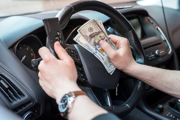 Male's hand sitting in car holding dollar and car key finance concept