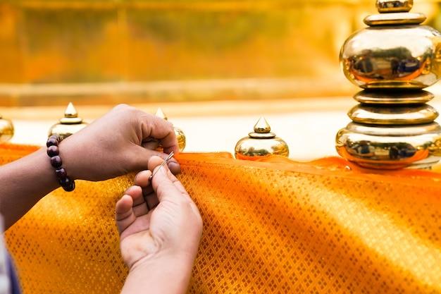 남성의 손은 탑 바리케이드를 덮기 위해 핀 걸쇠를 노란색 천에 함께 부착하려고합니다. 태국 전통 행사에서., 태국 북부.