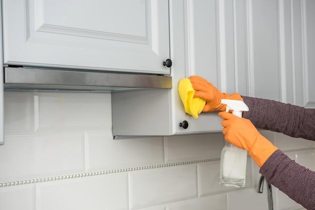 スプレーとスポンジでキッチンの木製家具を洗う黄色いぼろきれの手袋の男性の手。クリーニングコンセプト