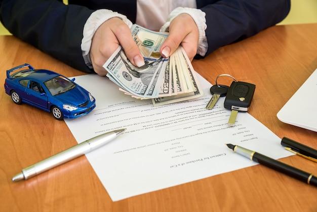 자동차 계약 청구 양식 및 계산기, 달러, 자동차에 서명하는 남자의 손
