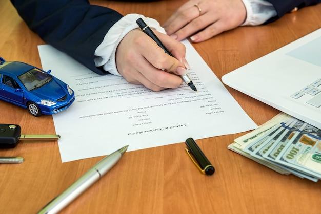 Руки мужчины подписывают форму заявки на контракт на автомобиль и калькулятор, доллар, автомобиль