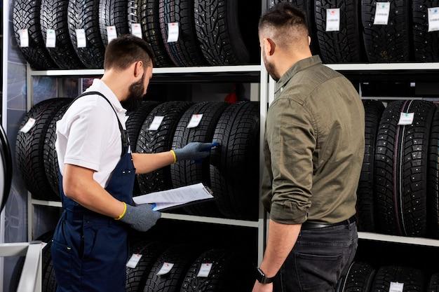 Продавец-мужчина показывает колеса покупателю-кавказцу в автосервисе и магазине автомагазина, они обсуждают и говорят о преимуществах шин