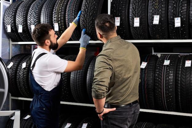 車の修理サービスや自動車店で白人男性の顧客にホイールタイヤを見せている男性のセールスマンは、タイヤの利点について話し合っています