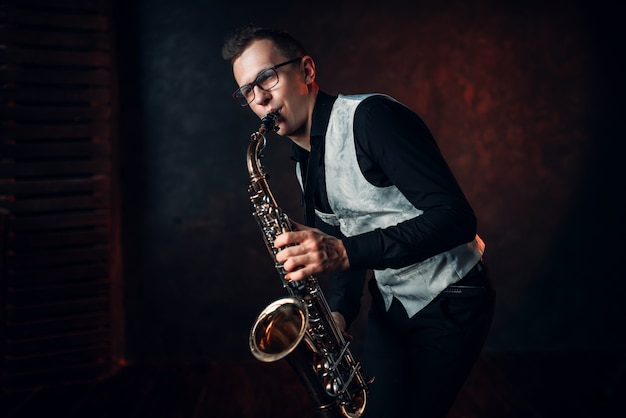 Male saxophonist playing classical jazz melody on sax.