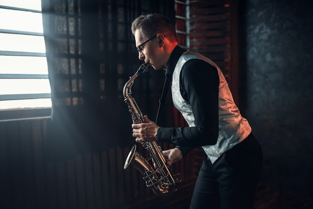 Male saxophonist playing jazz melody on saxophone against the window