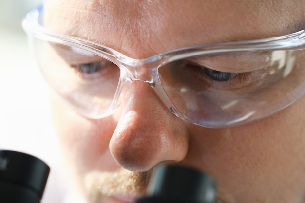 Male scientist looking through binocular