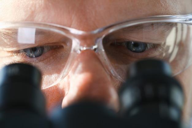 Мужской ученый смотрит в бинокль Premium Фотографии